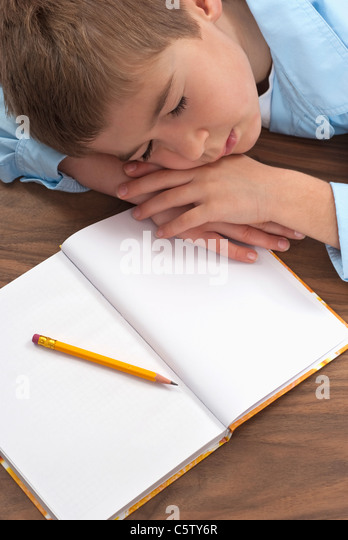 Schoolboy (6-7) sleeping at desk, elevated view - Stock Image