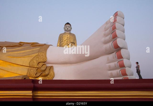 Feet of enormous reclining Buddha with Bodhi Tataung, giant standing buddha behind. Monywa, Myanmar (Burma) - Stock-Bilder