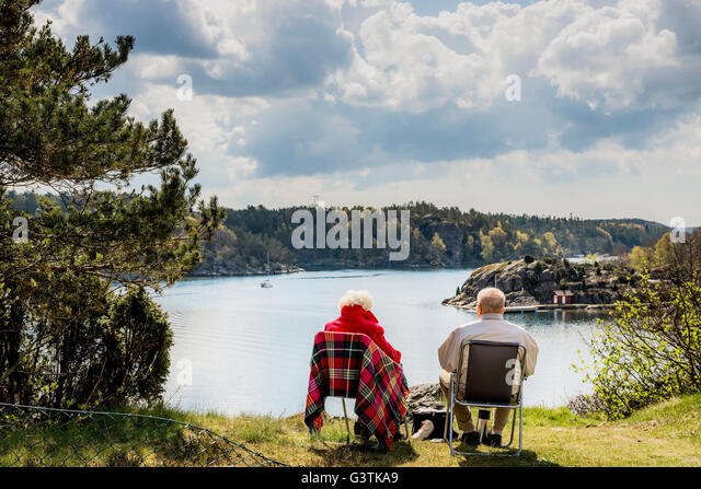 Sweden, West Coast, Bohuslan, Senior couple sitting on lounge chairs and looking at view - Stock Image