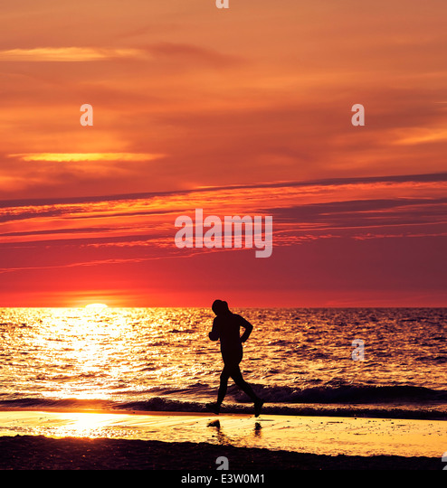 Woman running at beautiful sunset in the beach. - Stock-Bilder