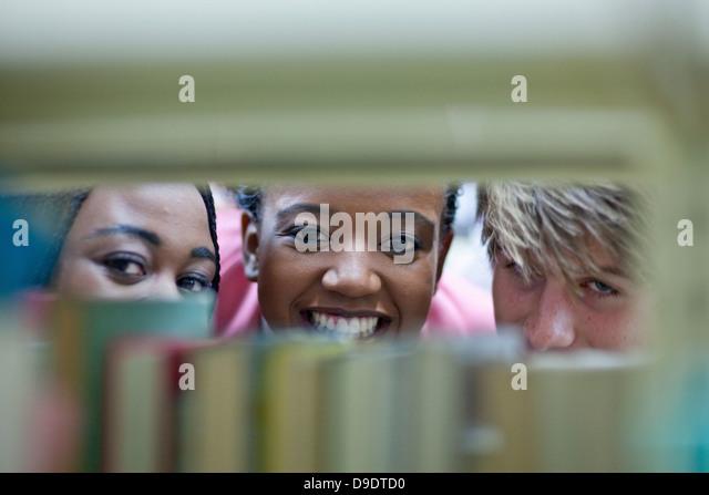 Three students peering through books - Stock Image