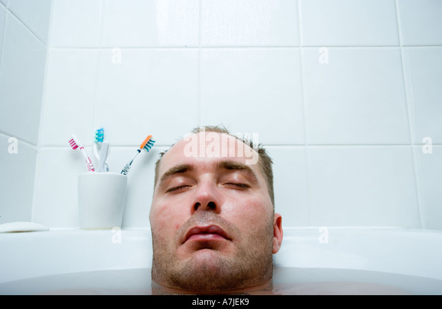 Head of a man with eyes closed and rest of his body immersed in bathtub - Stock-Bilder