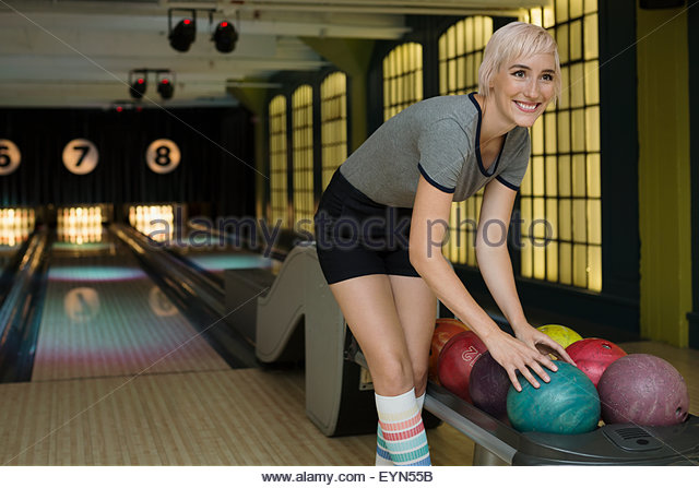 Smiling young woman choosing bowling ball from rack - Stock Image