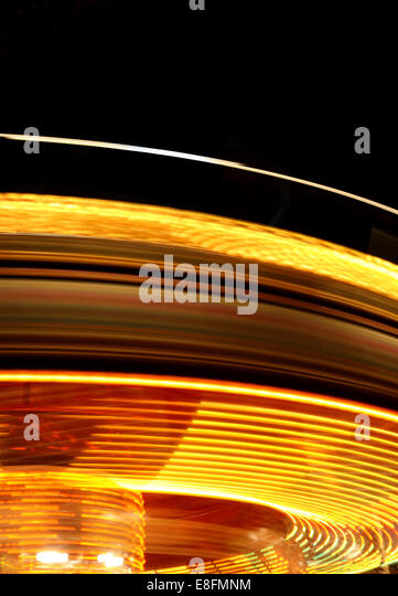 Rotating fairground ride at night - Stock Image