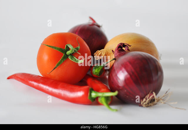 Tomato, red paper and onion on a white background close-up of the reflection - Stock Image