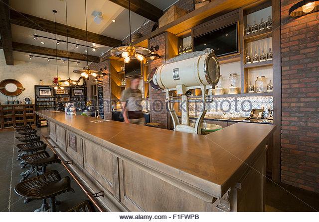 Worker walking behind counter at distillery bar - Stock Image