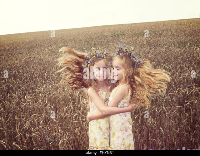 Girl with heralter ego in a wheat field - Stock Image