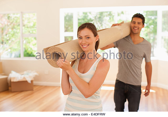 Couple carrying carpet into new house - Stock-Bilder