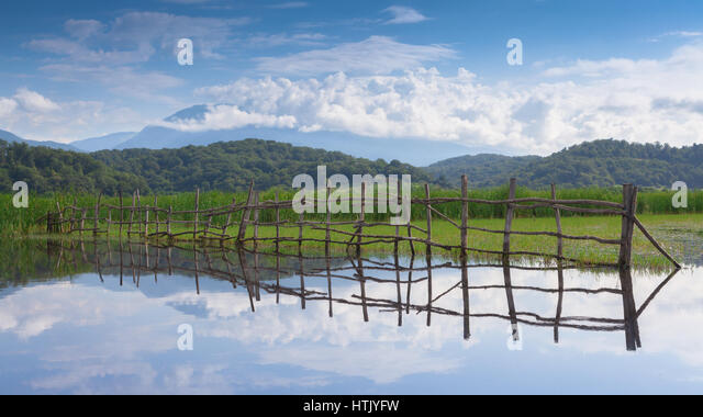 Homemade fence of wooden poles flooded with water near the lake Inkit - Stock Image