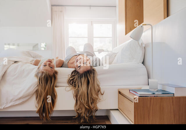 Young woman and a girl lying on bed. Mother and daughter in bedroom. - Stock Image