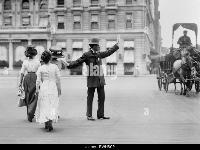 Vintage photo c1911 of a traffic cop in New York City halting a horse-drawn wagon to allow three women to cross - Stock Image