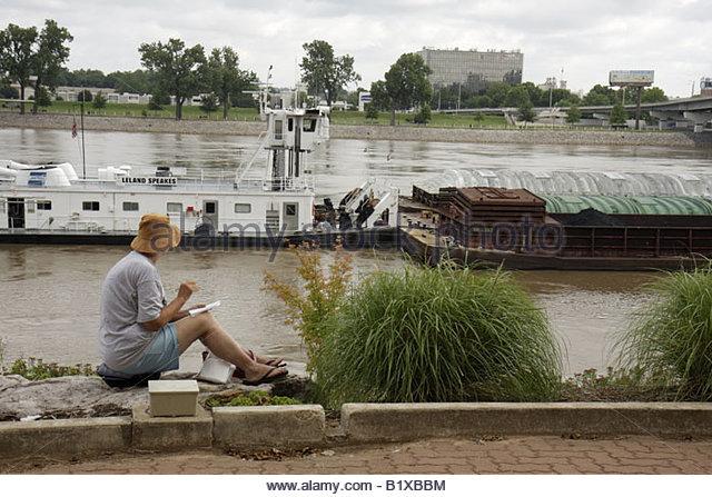 Arkansas Little Rock Arkansas River Breckling Riverfront Park woman sitting hat barge transport towboat navigation - Stock Image