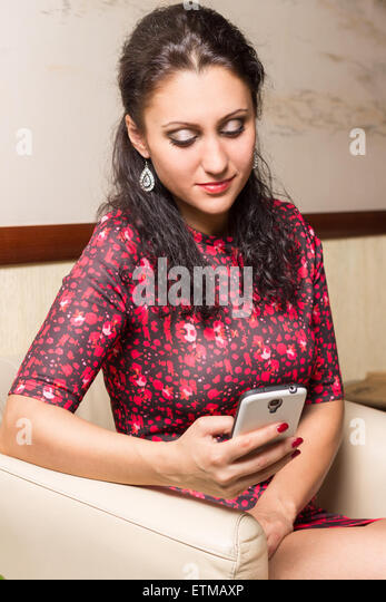 Young fashion brunette woman using smartphone sitting in a chair. Pretty caucasian girl texting message in a lobby - Stock Image
