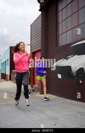 Two girlfriends having fun on their run in San Diego. - Stock Image