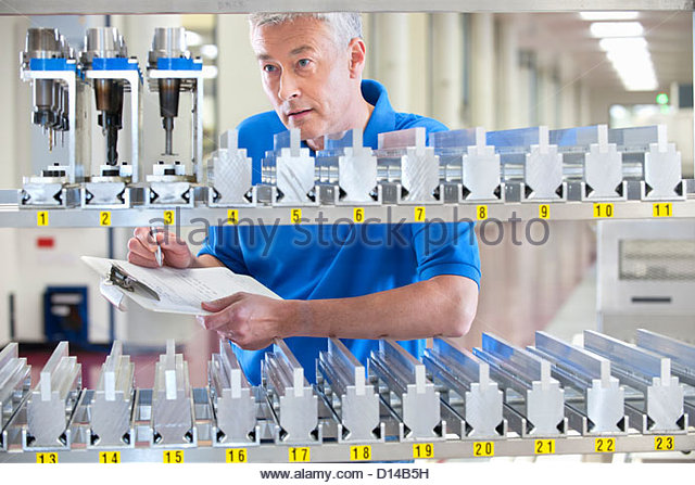 Technician checking inventory of machine parts in manufacturing plant - Stock Image