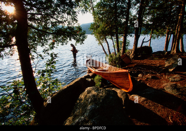 Fisherman wading in lake with canoe on shore - Stock Image