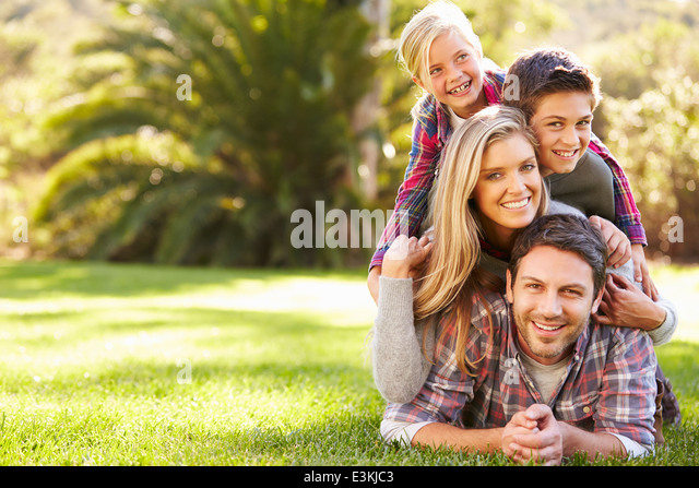 Portrait Of Family Lying On Grass In Countryside - Stock Image