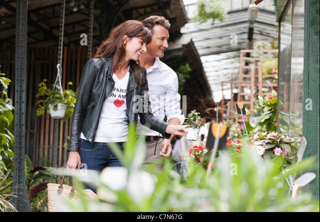 Couple choosing flowers at a stall, Paris, Ile-de-France, France - Stock Image