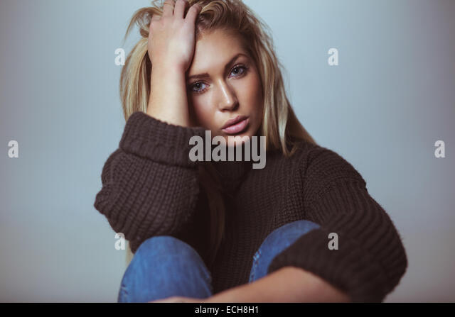 Image of beautiful female model wearing sweater with her hand in hair. Studio shot of attractive woman. - Stock Image
