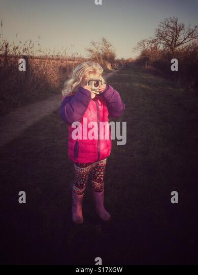 Young girl taking a picture with a toy camera - Stock-Bilder