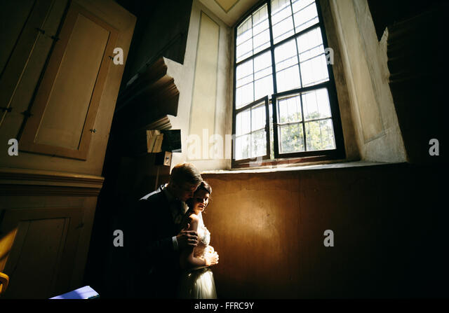 bride and groom on the background of a window. - Stock-Bilder