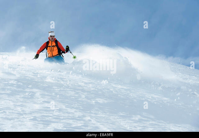 Man skiing downhill deep powder snow Alps - Stock Image