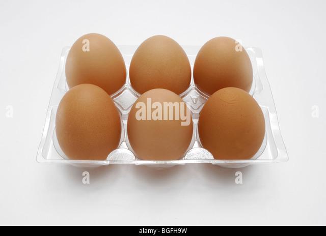 Six farm fresh brown chicken eggs in a plastic carton - Stock Image