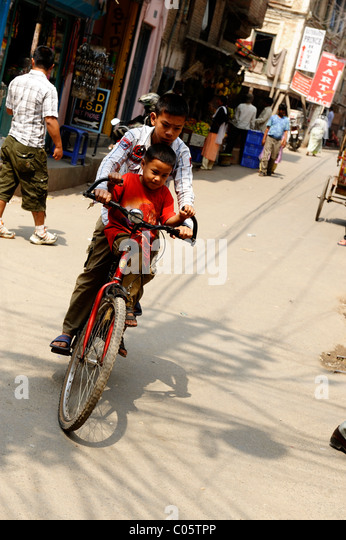 two boys riding  a bicycle , peoples lives ( the nepalis ) ,  life in kathmandu , kathmandu street life , nepal - Stock-Bilder