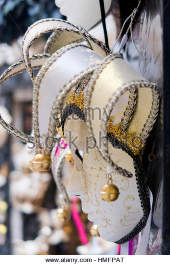 Close up ornate jester Venetian mask with bells for Venice Carnival hanging in market stall, Italy - Stock-Bilder