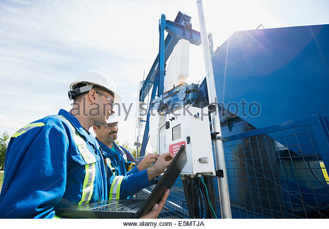 Workers checking oil well - Stock Image
