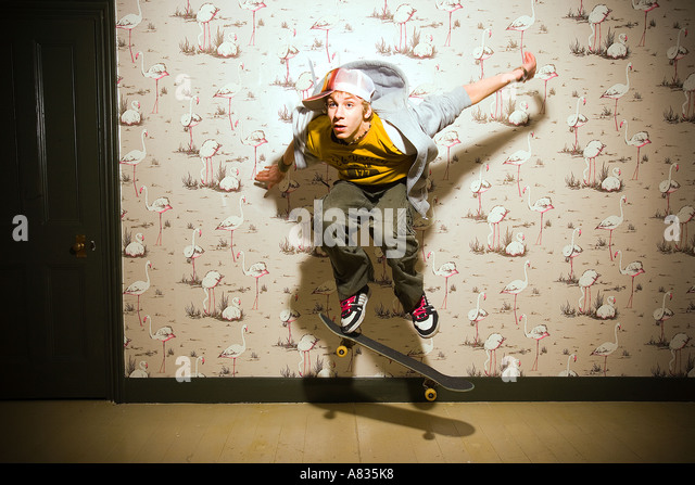A young boy jumping on his skateboard inside a room. - Stock Image