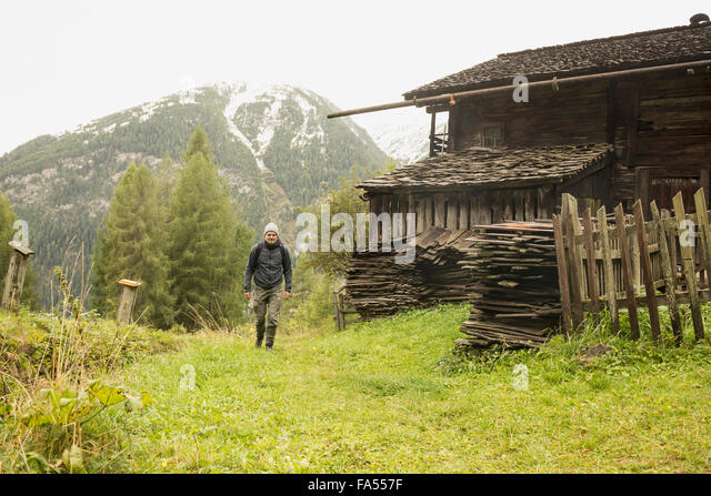 Mature hiker passing by cottage at rainy day, Austrian alps, Carinthia, Austria - Stock-Bilder