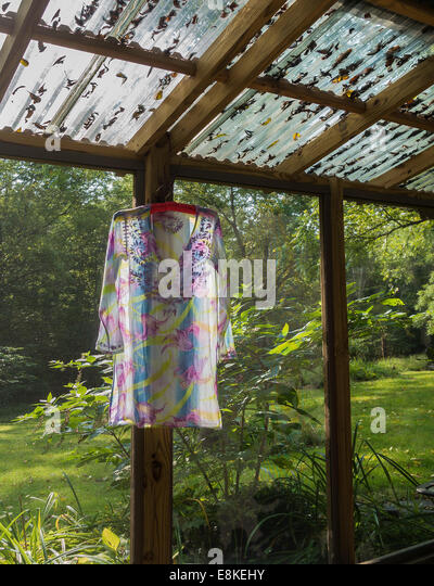 dress drying on hanger in screened porch - Stock Image