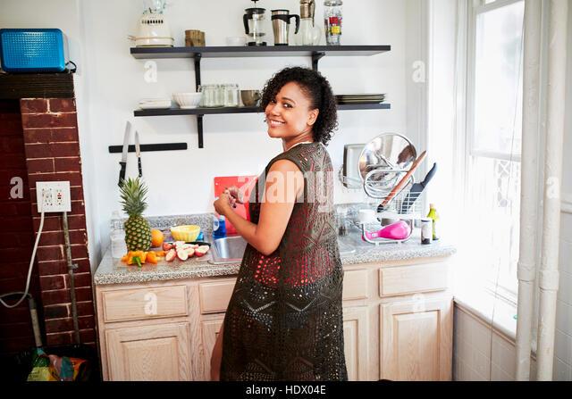 Smiling Mixed Race woman preparing fruit in kitchen - Stock Image