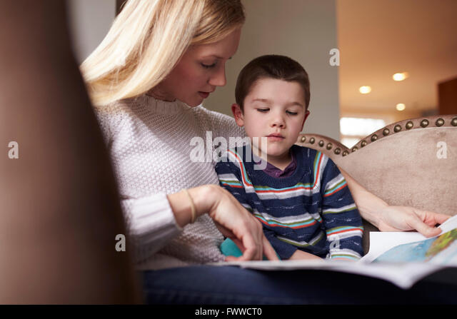 Mother Sitting In Chair At Home Reading Story To Son - Stock Image