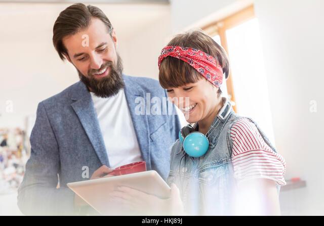 Smiling design professionals using digital tablet in office - Stock-Bilder