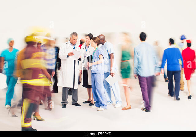 Workforce bustling around doctors and nurses - Stock Image