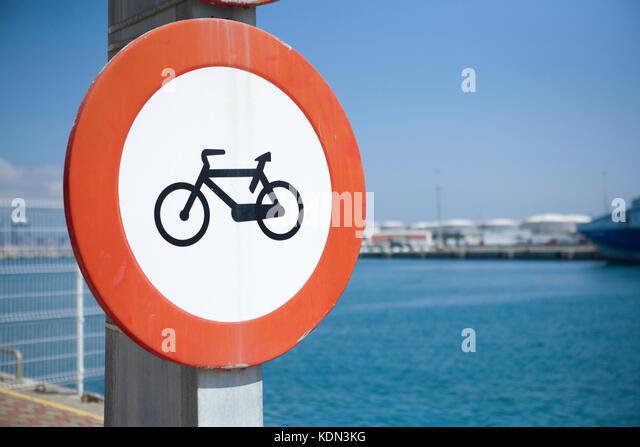 Bike lane symbol on blue background beside the seaport - Stock Image