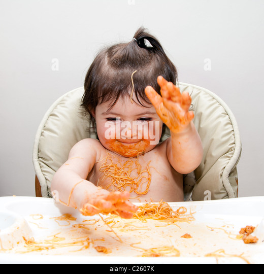 Happy baby having fun eating messy slapping hands covered in Spaghetti Angel Hair Pasta red marinara tomato sauce. - Stock Image