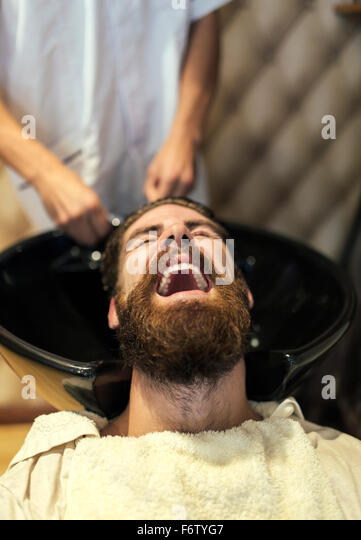Barber washing hair of a customer with open mouth - Stock Image