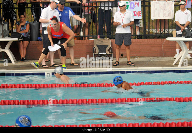 Fort Myer Swim Team coach Kristina Dorville encourages Squid breaststroke swimmers Vincent DiLeonardo, Thanos Zervos - Stock Image