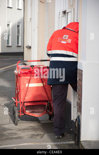 Royal Mail postman delivering letters with a trolley. - Stock Image