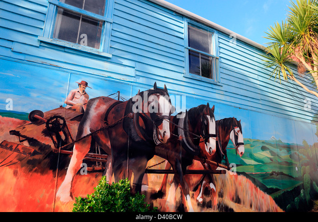 Draft horse plowing a field mural on wooden building in Marton, New Zealand - Stock Image