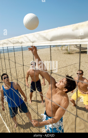Small group of young men playing volleyball on beach - Stock Image