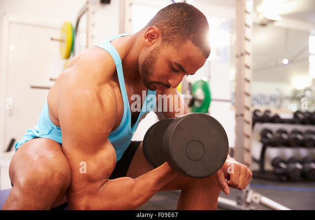 Man exercising with dumbbells at a gym, horizontal shot - Stock Image