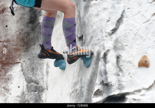 Young teen girl climbs up an artificial climbing wall close up of the feet and special climbing shoes - Stock-Bilder