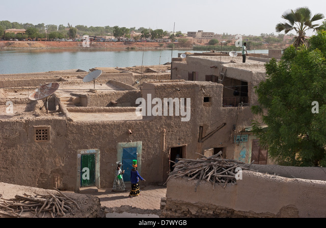 View over street and roof tops of traditionally built earthen mud buildings to River Niger, Mopti, Mali, West Africa - Stock Image