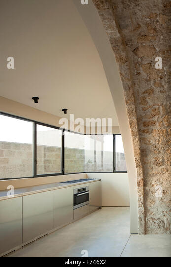 Exposed stone arch and minimalist kitchen in  House, Jaffa, Tel Aviv, Israel - Stock Image