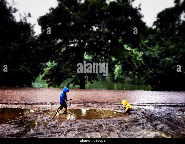 Twijfel kids playing in a puddle. - Stock Image