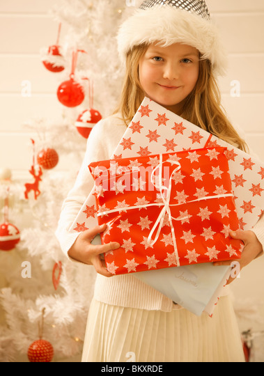 Close up of a girl standing by a Christmas tree holding gifts - Stock Image